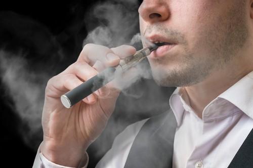 man smokes e-cigarette