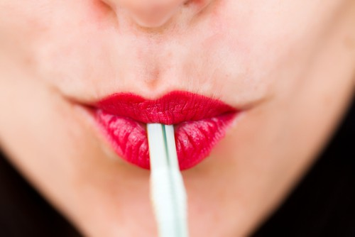 woman with red lips drinks from straw