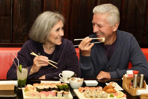 senior couple eating sushi