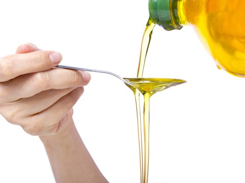 vegetable oil being poured over spoon