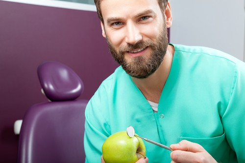 young male dentist with apple