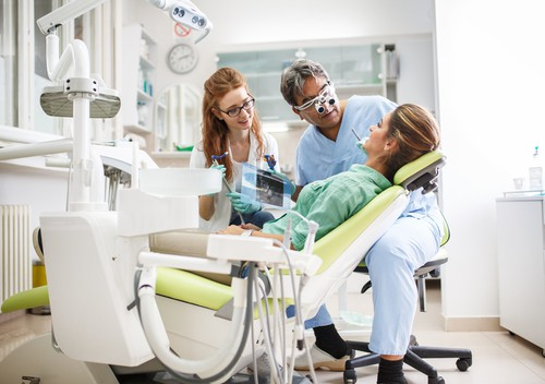 dentist and hygienist with female patient in chair